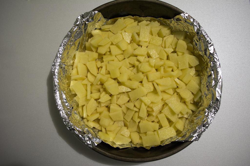 Нарезать картофель и выложить слоем в форму