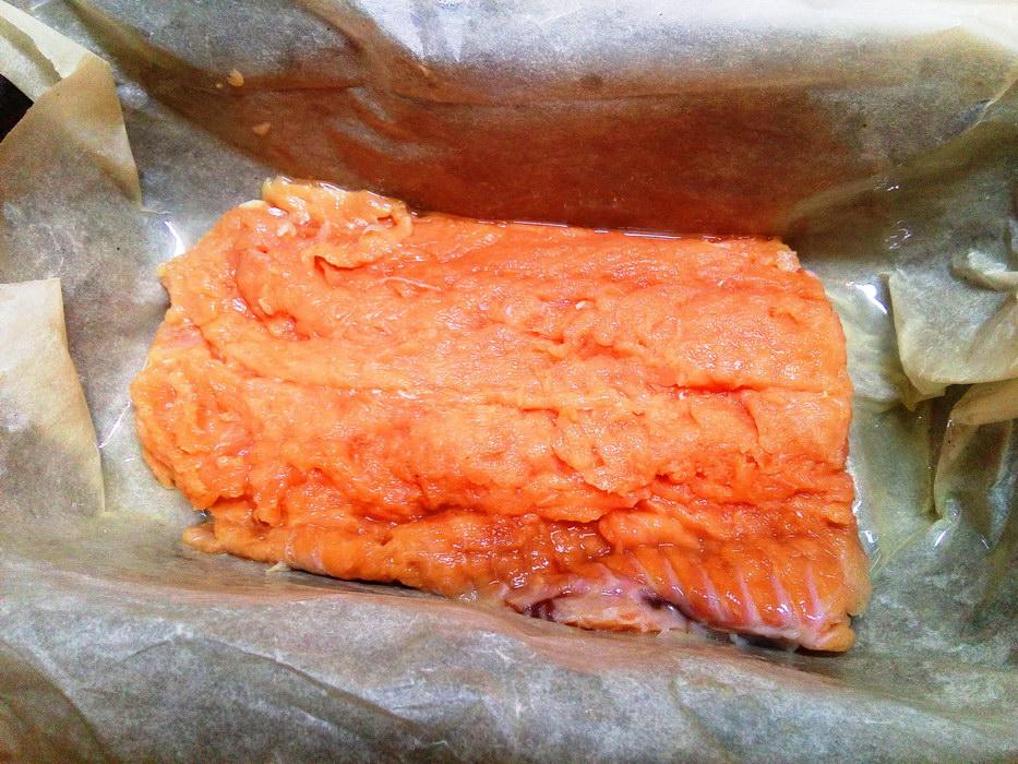Кладём филе красной рыбы на дно